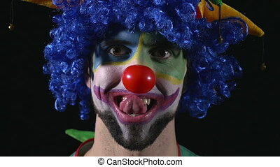 Close-up of young hilarious clown making funny faces