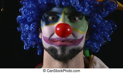 Closeup of clown making funny faces - Close-up of young...