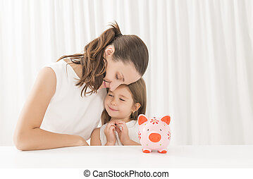 Family budget and savings concept - Mother and daughter...