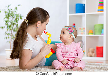 Happy family mom and baby daughter play musical toys