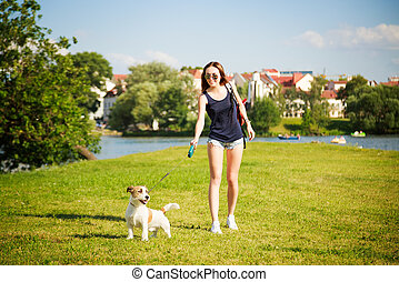 Young Woman with her Dog Walking in the Park