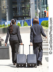 Two Women Business Travellers Walking With Rolling Suitcases...