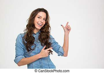 Cheerful attractive young woman smiling and pointing away