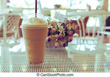 ice coffee frappe on table, plastic cup of coffee in cafe