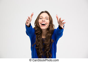 Cheerful excited young woman reaching hands to camera