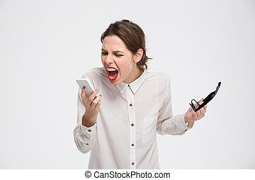 Angry irritated young business woman holding mobile phone...