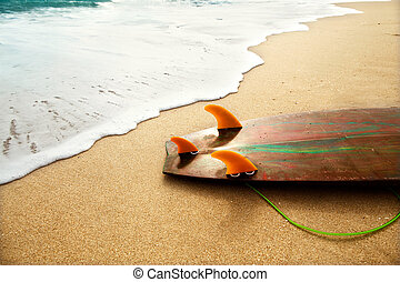 surf board lies on the beach in the waves