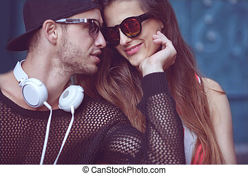 Young fashion couple kisses in the street