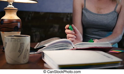 Young woman sitting at the table and thinks and writes