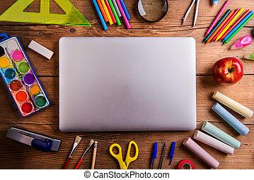 Desk, school supplies, closed notebook, wooden background -...
