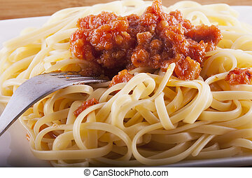 Spaghetti with sauce over white plate, horizontal image