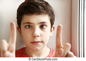 preteen handsome boy play squinting trick with his eyes and...