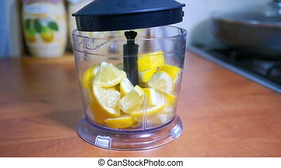 Sliced lemon poured into a blender