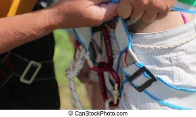 Man in a helmet strengthens sagety belt on girl