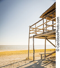 Beach Hut - Wooden beach hut with thatched roof looks out...