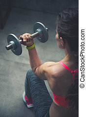 Seen from behind fitness woman lifting dumbbell - Body and...