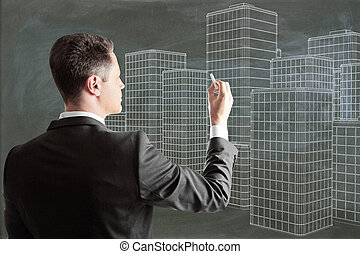 Man draws architectural design of buildings on blackboard
