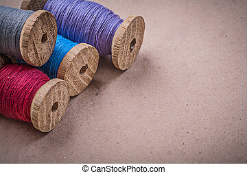 Wooden spools of sewing threads on vintage background