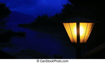 Yellow lantern in the dark with the blue twilight on background