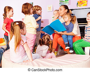 Teacher with kids read and discuss book - Teacher with kids...