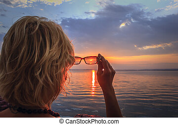 Blond woman looking at the sun.
