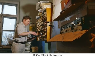 accounting clerk old man retro touches the paper in an old office
