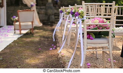 White chairs decorated with ribbons on wedding ceremony -...