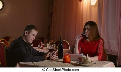 man and girl with smartphone and tablet in cafe evening love...