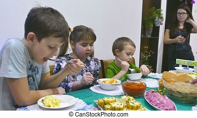 children eat at the feast - Children eat family breakfast...