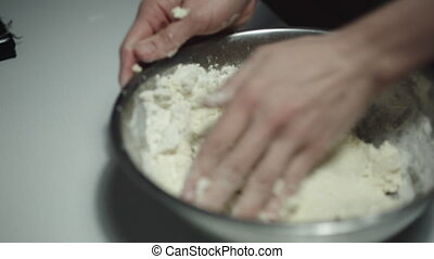 Woman kneading dough on the table close-up shot
