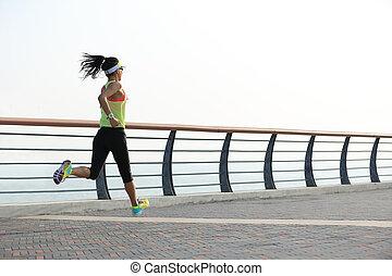 fitness woman runner running on seaside road