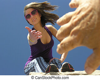 Helping Hand - Woman leaning over edge to help a hand...