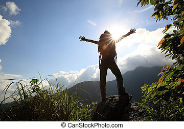 cheering young woman hiker open arms to sunrise on mountain...