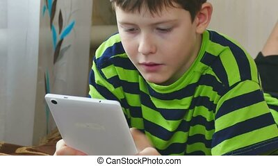 boy teenage playing on tablet game internet browsing - boy...
