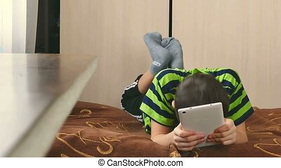 boy playing on tablet game internet browsing - boy playing...
