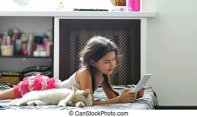 Teenage girl stroking a cat plays tablet