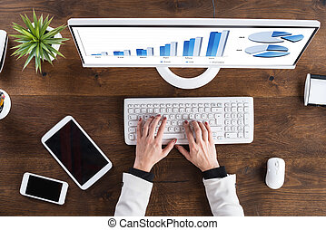 Businessperson Analyzing Graph On Computer - High Angle View...