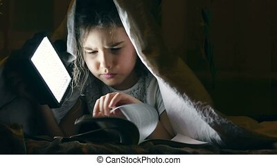 girl reading book night under covers with flashlight