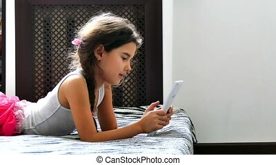 girl teen playing tablet game internet sitting on bed - girl...