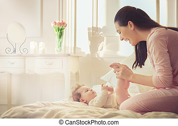 mother playing with her baby - happy family. mother playing...