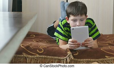 boy playing on tablet game internet - boy playing on tablet...