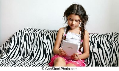 teen girl playing tablet game sitting on bed - teen girl...