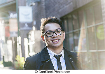Young asian man on city street - Young asian man wearing...