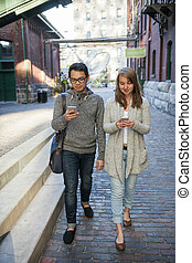 Two young people with smart phones - Two young people...
