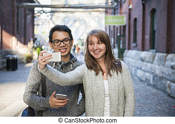 Two young people taking a selfie with smartphone