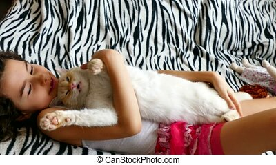 girl teenage love stroking cat lying on bed - girl teenage...