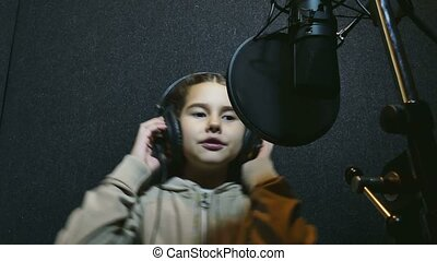 teen girl in headphones singing into microphone Professional...