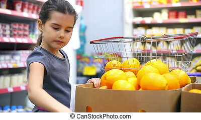 girl with tablet in supermarket to buy orange fruit - girl...