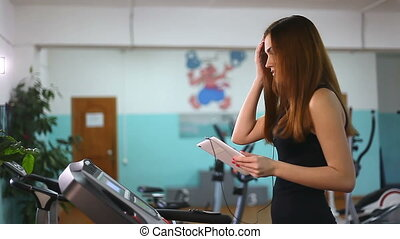 girl with the tablet on treadmill exercise at gym, healthy...