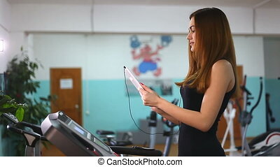 girl with tablet on treadmill exercise at gym, healthy...